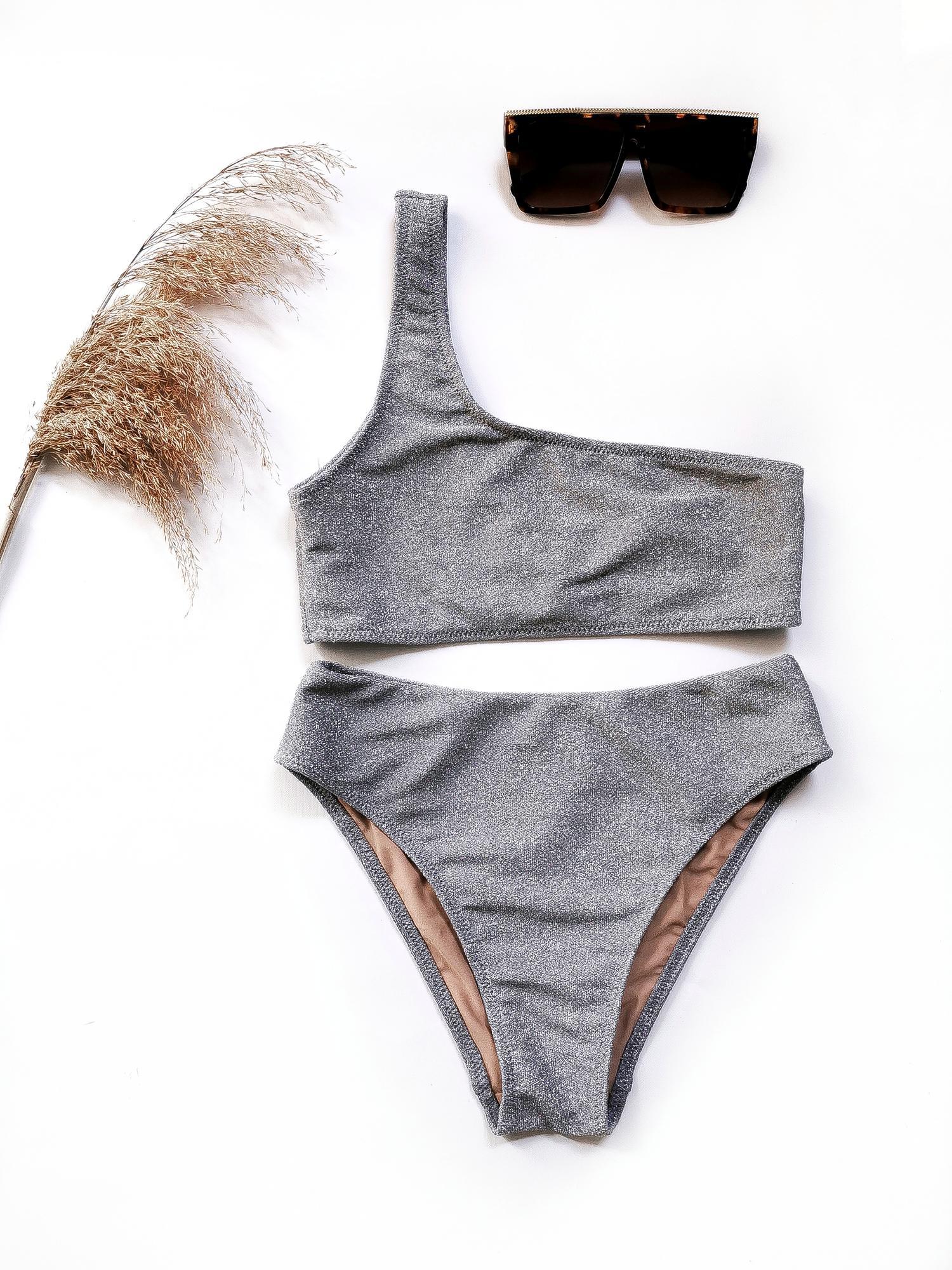 SILVER To kobiece bikini wykonane z materiału z błyszczącej nitki Lurex, który pięknie odbija światło, szczególnie na słońcu. Kostium niezwykle zwraca uwagę i idealnie komponuje się z opalenizną. Góra na jedno ramie, dół z delikatnie podwyższonym stanem. SKŁAD/MAIN FABRIC 56% poliester/polyamide 35% lurex 9% spandex PODSZEWKA/LINING 90% poliester/polyamide 10 % elastan/elastane Produkt szyty ręcznie w Polsce z najwyższych jakościowo materiałów.