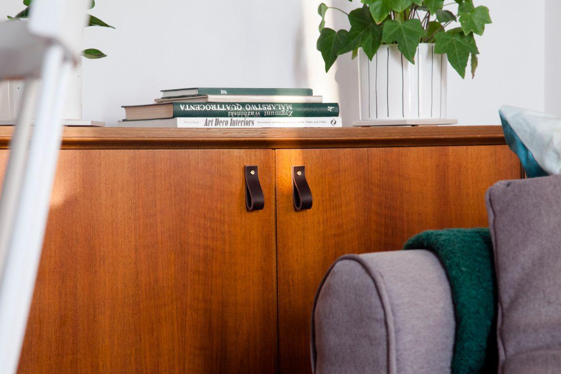 Uchwyt ze skóry Lade stanowi idealne uzupełnienie mebli nowoczesnych jak i tradycyjnych Jest to praktyczne a przy tym oryginalne rozwiązanie które ociepli każde wnętrze Wariant 4 uchwytu wykonany jest ze skóry barwionej na kolor ciemnobrązowy Materiały: skóra bydlęca garbowana roślinnie o grubości 3 4 mm śruba mosiężna lub stalowa M4 o długości 30 mm z nakrętką Wymiary: 20 mm szerokości 25 mm wysokości Uchwyt skórzany dostępny w czterech długościach: 50 mm po zawinięciu 70 mm po zawinięciu 102 mm po zawinięciu 126 mm po zawinięciu możliwe inne długości na zamówienie Skóra licowa to szlachetny materiał Aby pięknie się starzał należy dbać o niego korzystając z preparatów do pielęgnacji skóry licowej