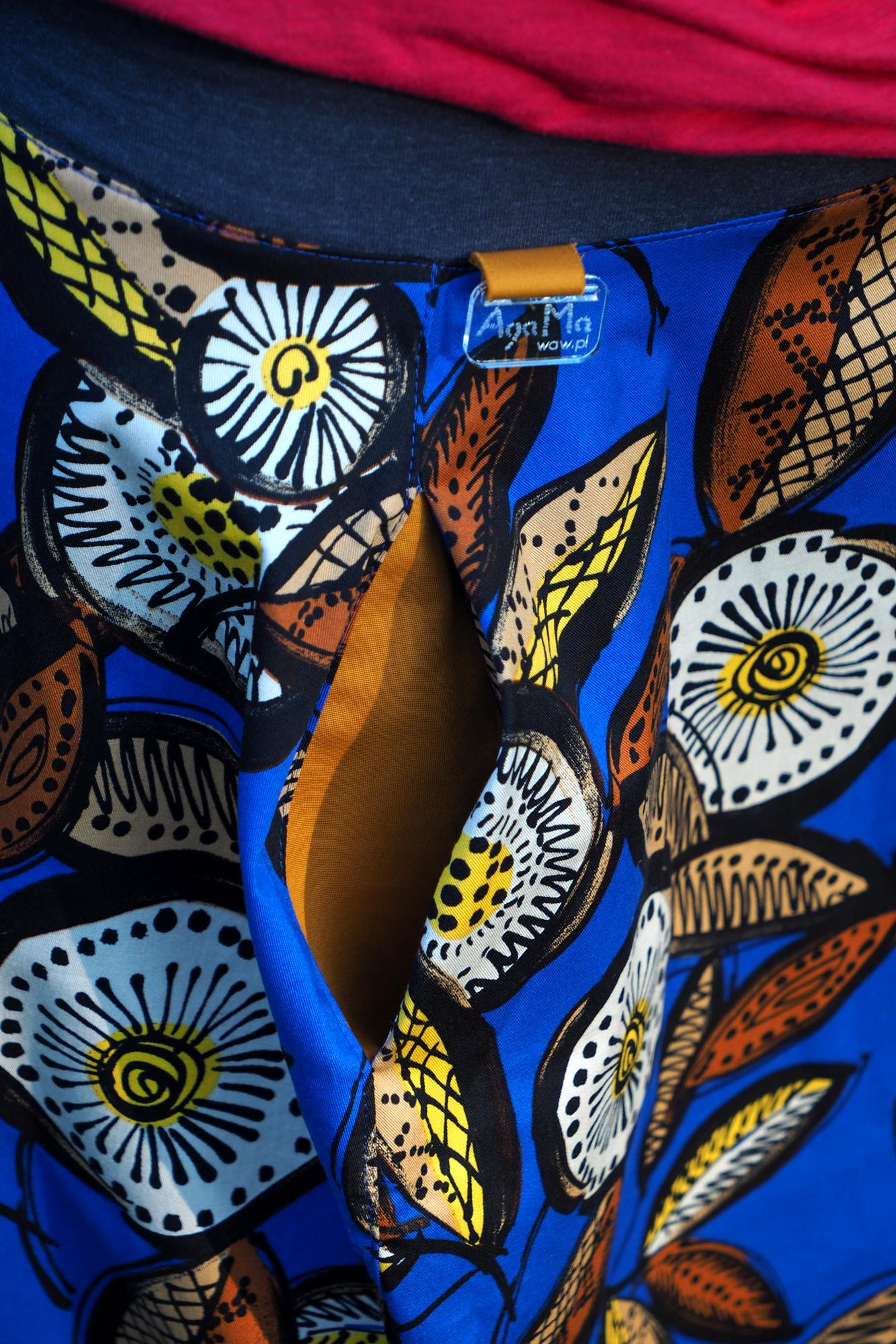 Krótka, niebieska spódnica w roślinne wzory. Z elementami koloru pomarańczowego i białego. Spódnica uszyta jest z bawełny, z 4 części mających kształt zaokrąglonych rombów. WYMIARY Modelka na zdjęciu ma 172 cm wzrostu. Obwód w biodrach: do 95 cm Długość spódnicy od ściągacza: 45 cm Długość górnego ściągacza: 9 cm To idealna spódnica dla Ciebie, ponieważ: - podkreśla kobiecość, - można ją nosić tak jesienią i zimą, jak i latem, - ma szeroki ściągacz w pasie zamiast gumek, zamków i pasków, - dzięki ww. ściągaczowi można ją nosić zarówno na wysokości pasa, jak i bioder, - praktyczne kieszenie pomieszczą niezbędne drobiazgi, - zapewnia swobodę i wygodę. - sprawdza się także przy zabawach i spacerach, również z dziećmi. STYLIZACJA Bardzo kobiecy efekt zapewni połączenie spódniczki z czółenkami i sandałami na obcasie. Również płaskie obuwie, typu baleriny czy sandałki sprawdzają się w tym zestawie. Do spódniczki można dopasować tak t-shirt, jak bluzkę z długim rękawem czy koszulę. Na chłodni