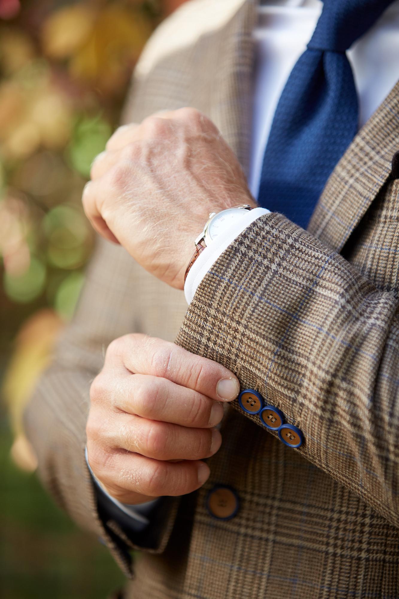 Marynarka uszyta z cienkiej tkaniny wełnianej w kratę księcia Walii. Brązowa krata o raporcie 6 x 7 cm na beżowym tle z dyskretną ciemnoniebieską kreską. Detale są dla nas ważne; ciemnoniebieski kolor pojawia się także w obramowaniu rogowych guzików. Marynarka pasowana, blisko ciała, bez podszewki, poduszek i zbędnych usztywnień. Zapięcie na dwa guziki, cięta kieszonka na poszetkę, dwie nakładane kieszenie zewnętrzne, dwie kieszonki wewnętrzne, dwa rozcięcia z tyłu. Funkcjonalne dziurki przy rękawach. Doskonała baza dla stylizacji mniej formalnych (smart casual) i nieformalnych (casual). Skład: Tkanina podstawowa: 100% wełna Podszewka w rękawach: 100% wiskoza Lamówki: 100% bawełna: