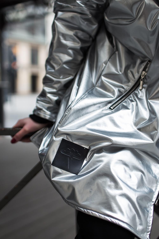 Parka o luźnej, oversizeowej formie z ciepłej tkaniny imitującej lateks o srebrnym metalicznym kolorze. Płaszcz posiada bawełnianą podszewkę w kolorze czarnym. Lekko opuszczona linia ramion, zapięcie na metalowy suwak oraz obszerny kaptur dodają mu charakteru. Na froncie dwie kieszenie zapinane na metalowe suwaki. Przeskalowana, swobodna forma zapewnia komfort i wygodę w chłodniejsze dni.