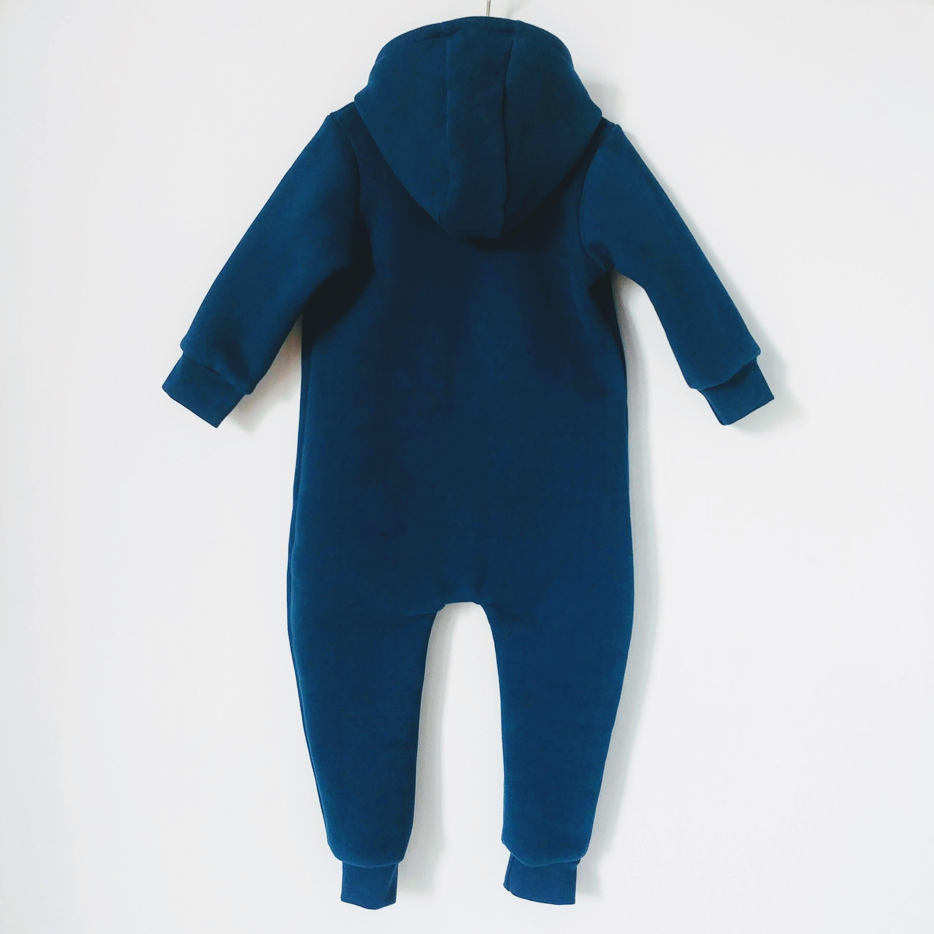Dziecięcy kombinezon w kolorze morskim, niesamowicie gruby, niezwykle ciepły i szalenie miły w dotyku . Idealny dla niemowląt do wózka, czy fotelika samochodowego. Zaprojektowany i uszyty w Polsce. Zapinany na napy.Posiada kaptur oraz ściągacze na nogawkach i rękawkach. Bawełna ma doskonałe właściwości cieplne,ponadto zapewnia doskonałą cyrkulację powietrza ,a dodatkowo bawełna drapana,jest wyjątkowo miękka i miła w dotyku. Dzianiny wykonane ze 100% bawełny, pomimo swojej 100% naturalności, cechują się dużo mniejszą odpornością mechaniczną, która w przypadku dzieci jest niezwykle istotna. Wielokrotne pranie i rozciąganie ( w newralgicznych miejscach, np. łokciach) może powodować deformowanie dzianiny, a tym samym struktury płaszcza. Zastosowane przez nas dzianiny cechują się wysoką wytrzymałością przy zachowaniu naturalnych właściwości bawełny. Kombinezon dziecięcy dostępny w rozmiarach 68/7 4,80/86 oraz 92/98.