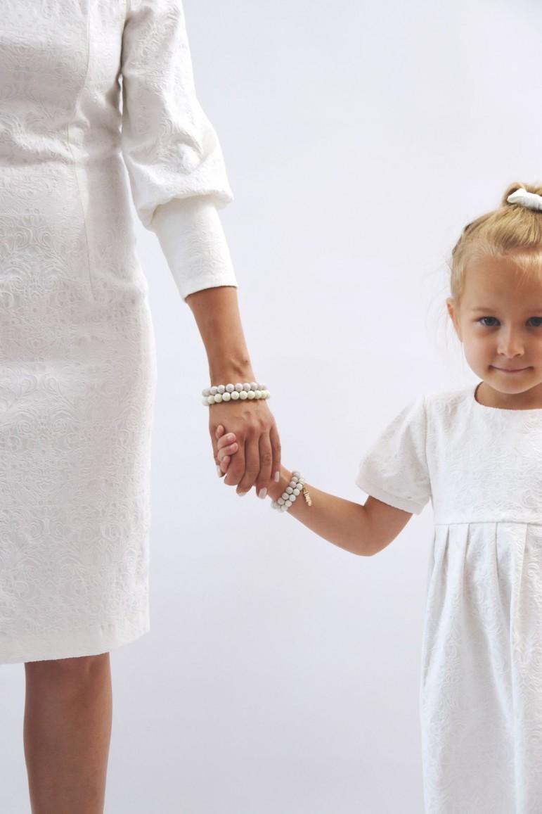 Elegancka sukienka dla dziewczynki wykonana z bardzo efektownej tkaniny, o niespotykanie ciekawej fakturze. Delikatne bufki na rękawkach nawiązują do sukienki mamy, dzięki czemu można stworzyć komplet sukienek mama i córka na wiele uroczystości wymagających szczególnej oprawy. Sukienka dzięki krojowi i materiałowi może być propozycją całoroczną. Ponadczasowy fason, piekne marszczenie pod karczkiem oraz materiał czynią tę sukienkę wyjątkową i jedyną w swoim rodzaju. Wymiary sukienek na płasko: 68/74 - długość sukienki: 39,5 cm; szerokość pod pachami: 25,5 cm 80/86 - długość sukienki: 44,5 cm; szerokość pod pachami: 27 cm 92/98 - długość sukienki: 49 cm; szerokość pod pachami: 28 cm 104/110 - długość sukienki: 54 cm; szerokość pod pachami: 29,5 cm 116/122 - długośc sukienki: 58,5 cm; szerokość pod pachami: 31 cm 128/134 - długość sukienki: 64 cm; szerokość pod pachami: 33 cm 140/146 - długość sukienki: 73,5 cm; szeroość pod pachami: 35 cm