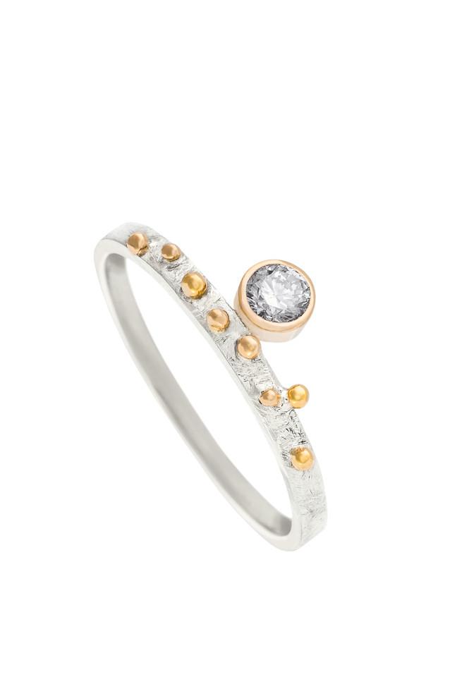 Delikatny pierścionek z diamentem, wykonany ręcznie z białego i żółtego złota p 0,585. Osadzony diament waży 0,11ct, mierzy 3 mm średnicy. Uroczy i kobiecy, będzie pasował każdej miłośniczce prostej, ale i oryginalnej biżuterii. Na zamówienie dostępny we wszystkich rozmiarach i z diamentami o dowolnej wielkości. Czas oczekiwanie na wykonanie zamówienia wynosi od dwóch do trzech tygodni.