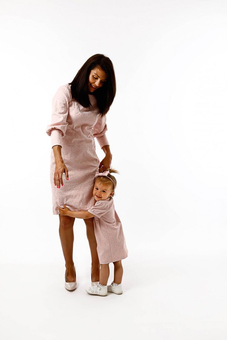 Sukienki dla mamy i córki z kolekcji New Royal to bardzo elegancka i nietuzinkowa propozycja na szczególne okazje, wymagające wyjątkowej oprawy jak chrzest, komunia, ślub, święta itp. Sukienki uszyte z tej samej tkaniny z piekną fakturą i wytłaczanym wzorem w kolorze pudrowego różu - różnią się między sobą fasonem, ale razem tworzą piękną całość. Wspólny element to bardzo efektowny rękaw zarówno u mamy, jak i u córki. Damska sukienka posiada pięknie układającą się bufę, która zakończona jest obcisłym ściągaczem, co dodaje stylizacji szyku. Sukienka córeczki posiada zaś małą bufkę u góry rękawa, co czyni sukienkę bardzo delikatną i słodką. Dodtatkową zaletą tego zestawy mama i córa jest fakt, że dzięki materiałowi i krojowi miże być to propozycja całoroczna. Jeśli chcecie wyróżnić się w ten szczególny dzień jak chrzest, ślub, ważna uroczystość to zestaw mama i córka z kolekcji New Royal jest strzałem w dziesiątkę. UWAGA! Od teraz istnieje możliwośc wyboru sukienki damskiej standard oraz