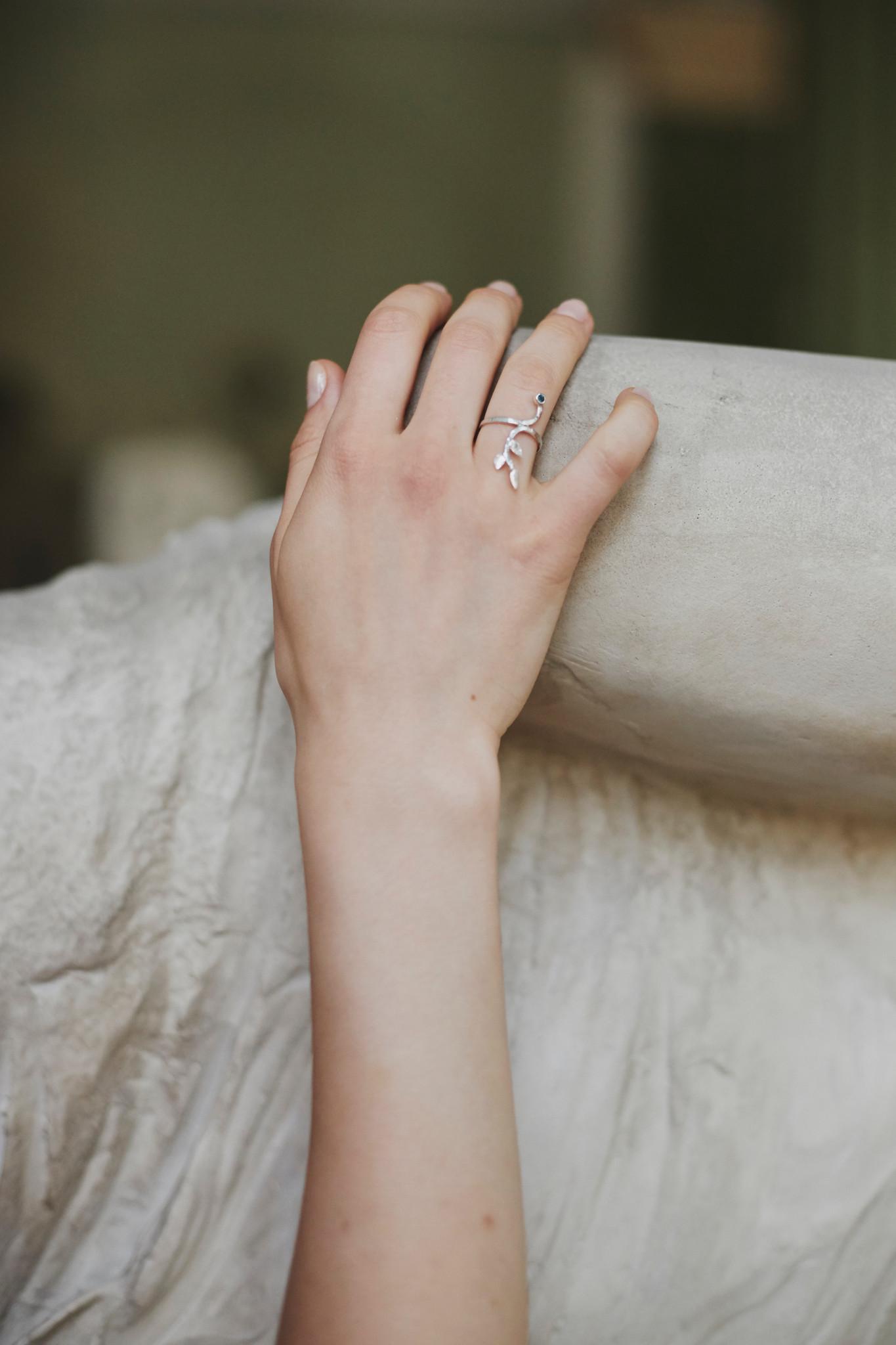 Pamiętacie starożytny mit o Dafne? Dafne była nimfą, której urodą zauroczył się Apollo. Nimfa jednak nie odwzajemniała jego względów, uciekając przed nim zamieniła się w drzewo laurowe. Bardzo zachwyca mnie rzeźba Berniniego ukazująca moment przemiany Dafne, z jej palców wystrzeliwują listki, miękkie i delikatne ciało zmienia się w korę drzewa. Pierścionek jest moją interpretacją tej przemiany, listki noszone na palcu w symboliczny sposób mogą to obrazować. Długi pierścionek jest ręcznie wykonany ze srebra p 0,925 i pozłocony 24k złotem. Długość całkowita ok 2,5 cm, kamień: niebieski szafir 2mm.
