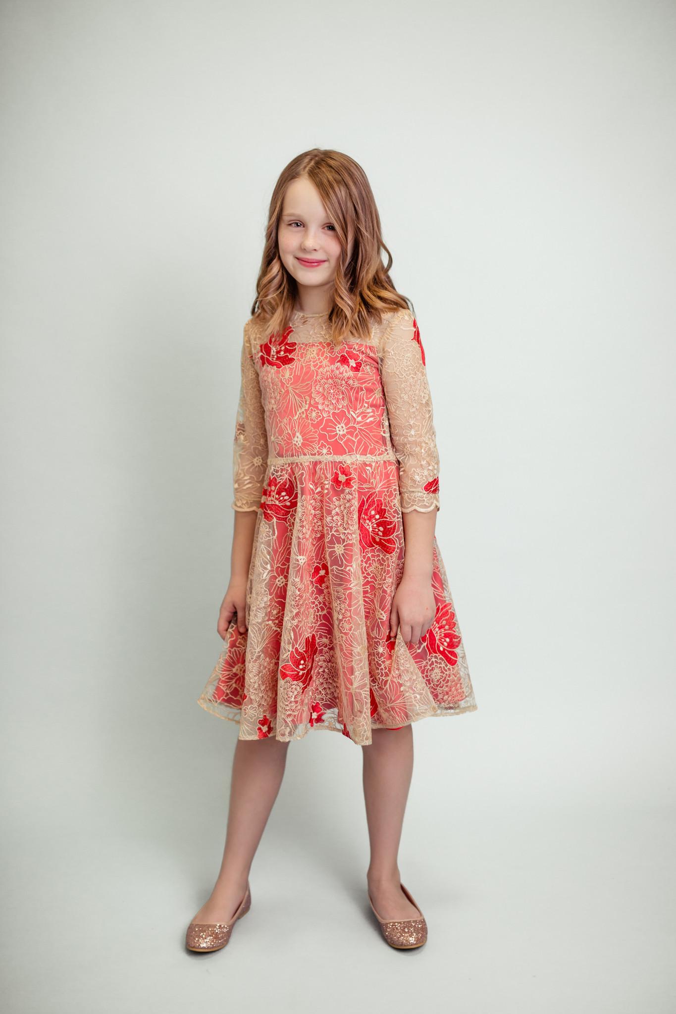 Rozkloszowana sukienka wykonana z pięknej, wysokiej jakości koronki  o kwiatowym motywie w kolorze cielistym na tle czerwonej satynowej tkaniny,   z tyłu zapinana na ukryty zamek.  Półokrągły dekolt. Rękaw 3/4.  Idealna na wesele, święto, chcrzest, urodziny i inne wyjątkowe okazję. Skład wiskoza 100%