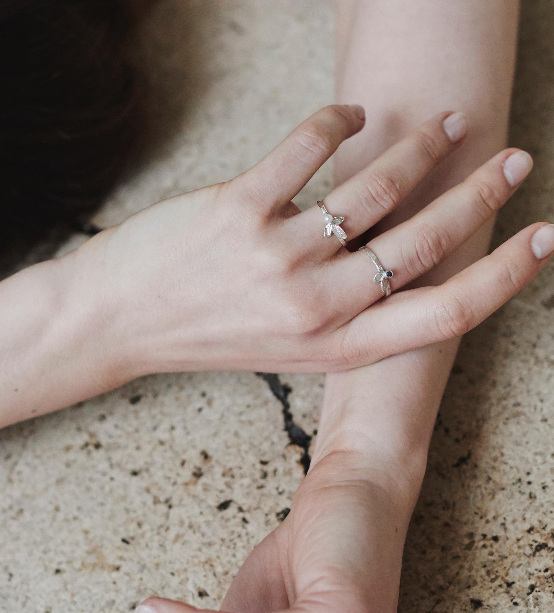 """Uroczy i delikatny pierścionek z kolekcji Arche. Trzy drobne listki o chropowatej fakturze tworzą piękną kompozycję z malutką perełką. Idealny do noszenia """"na codzień"""". Listki są specjalnie zaokrąglone i wygładzone tak, by nie kuły ani nadmiernie nie zahaczały o ubrania. Wykonany ręcznie ze srebra p 0,925. Perła naturalna, hodowlana, słodkowodna wielkość ok 2-3 mm"""