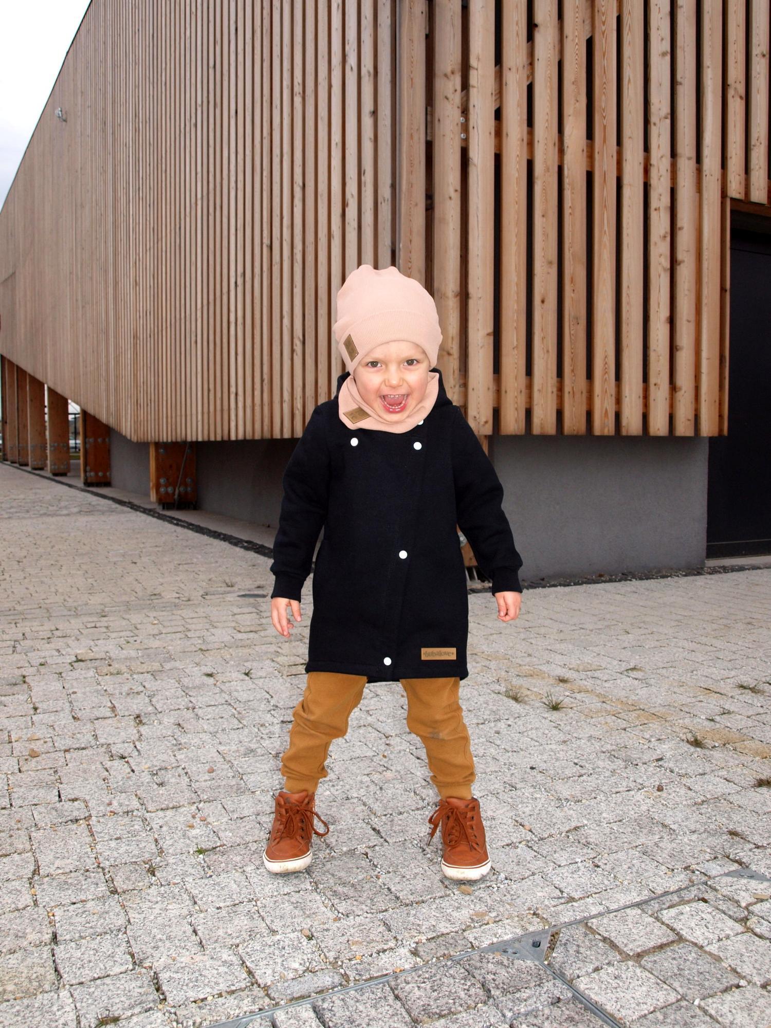 """Płaszcz dziecięcy dzianinowy wiosenno jesienny w kolorze czarnym, stworzony z myślą o najmłodszych. Uszyty z dzianiny bawełnianej z 10% dodatkiem poliestru. Bawełna ma doskonałe właściwości cieplne. Zapewnia doskonałą cyrkulację powietrza , dodatkowo bawełna drapana, wyjątkowo miękka i miła w dotyku. Dzianiny wykonane ze 100% bawełny, pomimo swojej 100% naturalności, cechują się dużo mniejszą odpornością mechaniczną, która w przypadku dzieci jest niezwykle istotna. Wielokrotne pranie i rozciąganie (w newralgicznych miejscach, np. łokciach) może powodować deformowanie dzianiny, a tym samym struktury płaszcza. Zastosowane przez nas dzianiny cechują się wysoką wytrzymałością przy zachowaniu naturalnych właściwości bawełny. Udoskonalona forma płaszcza zapewnia ochronę przed wiatrem dzięki głębokiemu kapturowi i wysokiemu kołnierzowi. Zakładka z tyłu płaszcza zapewnia swobodę ruchów podczas zabawy, nie ogranicza kucania ,siadania i innych akrobacji. Długość  """"za pupę """" zapewnia ciepło w każ"""