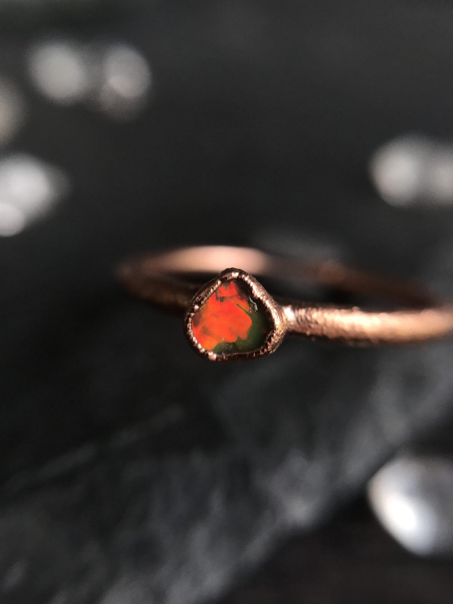 Ręcznie robiony pierścionek z małym, pomarańczowo-zielonym opalem w miedzianej oprawie. Pierścionek jest niepowtarzalny, zrobiony na wzór tego będzie zawsze inny. Otrzymasz dokładnie tę sztukę pokazaną na zdjęciach. Rozmiar pierścionka to 13. Opal to kamień urodzinowy osób urodzonych w październiku, będzie to fajny prezent dla osoby urodzonej w paździeniku lub upamiętniający osobę w tym miesiącu urodzoną.