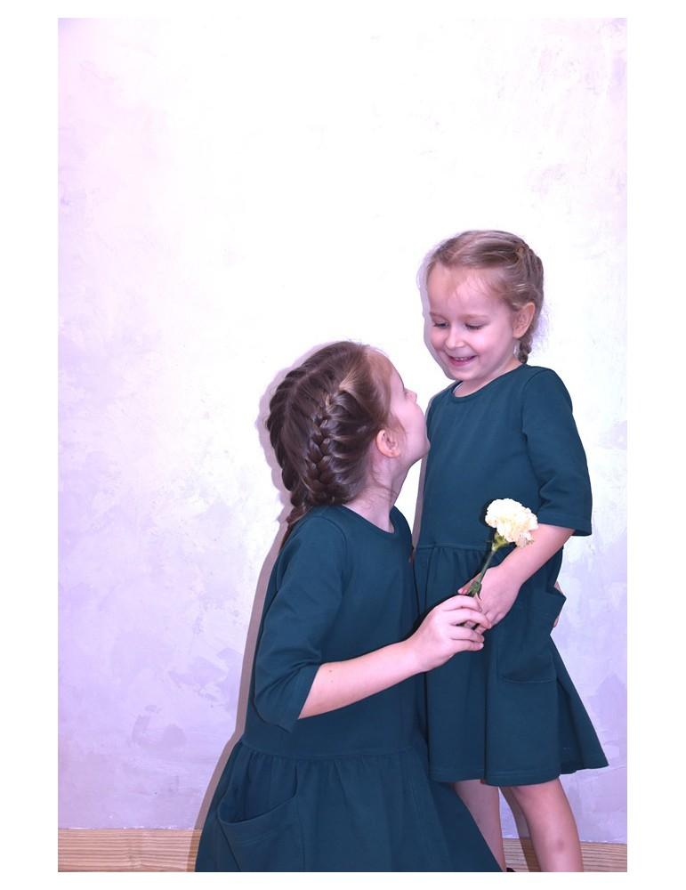 Komplet takich samych sukienek dla dziewczynek to idealne rozwiązanie, aby uszczęśliwić i wyróżnić wasze pociechy, podkreślić siostrzaną więź i miłość oraz dać piękną pamiątkę dzieciństwa. Oversize'ove luźne i wygodne sukienki w pięknej butelkowej zieleni to propozycja na szczególne okazje oraz na co dzień. Duże kieszenie dodają uroku całej stylizacji, czynią ja bardzo praktyczną i sprawiają, że Wasi milusińscy pokochają tę stylizację. Dokładny opis tej sukienki znajdziesz tutaj.