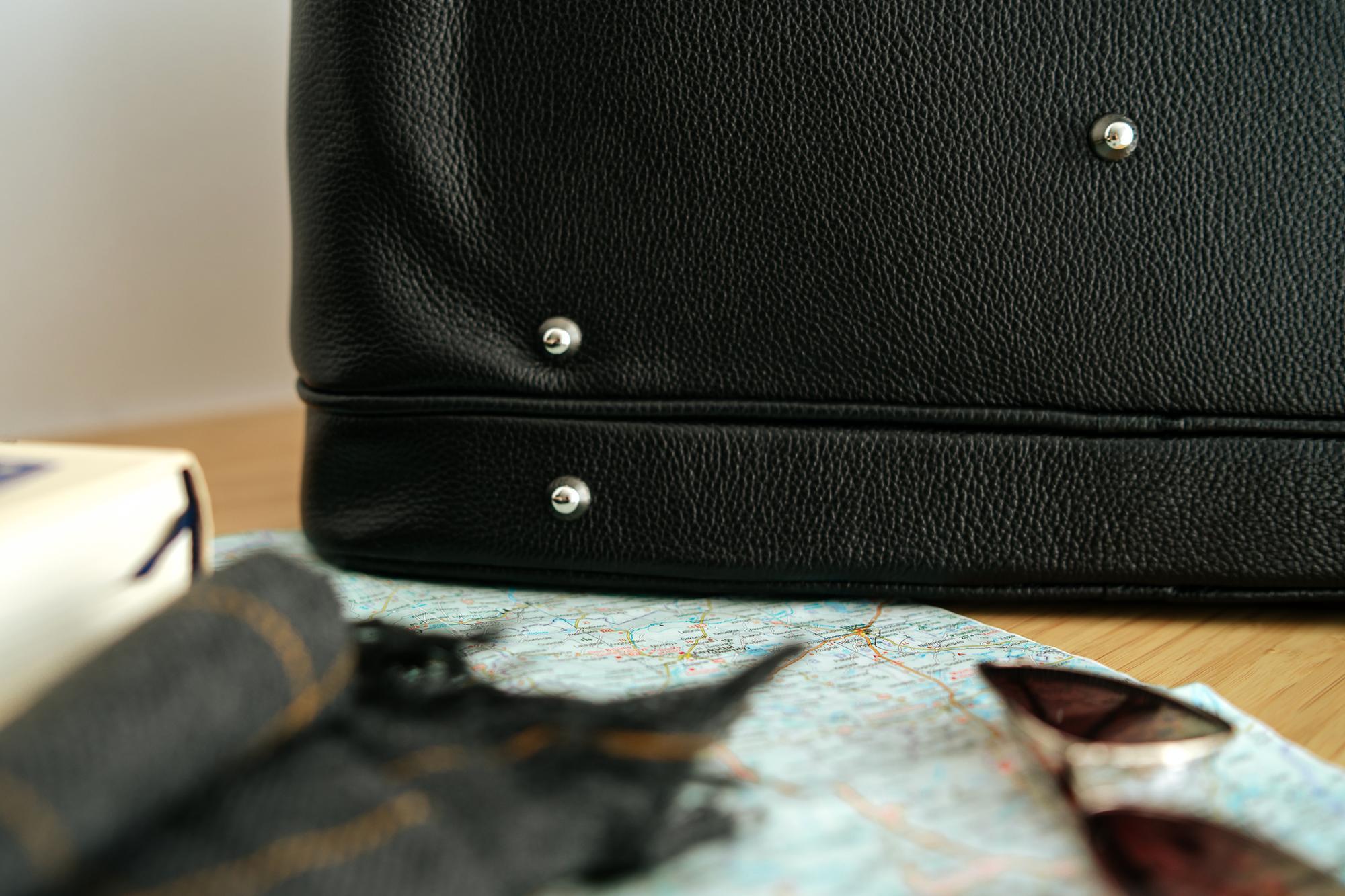 Starannie wyselekcjonowana, odporna na zarysowania, naturalna skóra groszkowa w wyjątkowym odcieniu głębokiej czerni srebrne dodatki jakości premium, podszewka w kolorze eleganckiej czerwieni i niezwykła precyzja wykonania sprawiają, że podróżna torba Nashe to rzemiosło z najwyższej półki! pojemna - elegancka wersja praktycznej torby podróżnej uszyta z naturalnej skóry groszkowej najwyższej jakości stworzona według autorskiego projektu wykonana w polskiej pracowni z miłością, pasją i w zgodnie ze sztuką kaletniczą wyposażona w długi, regulowany, odpinany pasek wykończona odpornymi na zarysowania srebrnymi okuciami wykończona chroniącymi przed zarysowaniami skóry od spodu srebrnymi nóżkami zapinana na metalowy zamek błyskawiczny wyłożona elegancką czerwoną podszewką z delikatnym satynowym połyskiem funkcjonalna - 9 kieszeni: główna + 2 boczne zamykane na zamek + 3 płaskie na dokumenty + 1 wypukła na smartfon + 2 wewnętrzne zapinane na zamek zapakowana w wytrzymałe szykowne pudełko do pr