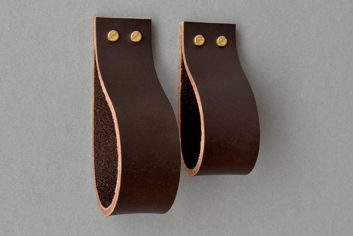 Uchwyt meblowy Lade Maxi to wykonany z naturalnej skóry dodatek do mebli w różnych stylach Wykorzystanie dwóch śrub podkreśla szerokość skórzanego paska i stanowi oryginalne rozwiązanie Wariant 4 wykonany jest ze skóry naturalnej barwionej na kolor ciemnobrązowy Materiały: skóra bydlęca garbowana roślinnie o grubości 3 4 mm 2 śruby mosiężne lub stalowe M4 o długości 30 mm z nakrętkami Wymiary: 35 mm szerokości 30 mm wysokości po zamontowaniu Produkt jest dostępny w trzech długościach: 70 mm po zawinięciu 102 mm po zawinięciu 126 mm po zawinięciu Skóra licowa to szlachetny materiał Aby pięknie się starzał należy dbać o niego korzystając z preparatów do pielęgnacji skóry licowej