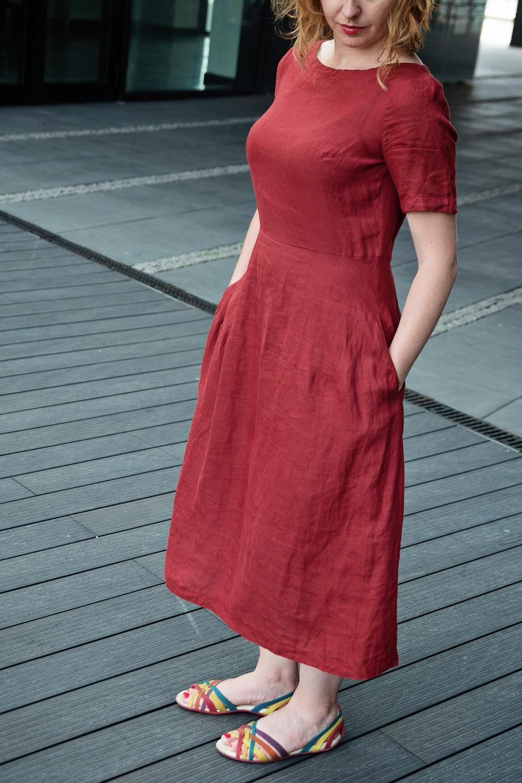 Lniana sukienka Ceglana, nasz bestseller w Kiecy. Jej odcień to kolor naszych gotyckich i neogotyckich cegieł, które na Pomorzu stanowią częsty widok. Szukając idealnego koloru zjechaliśmy pół Polski. Większość odcieni była zbyt intensywna albo zbyt marchewkowa. Ale w końcu się udało. Sukienka jest dostępna w dwóch długościach: midi – czyli do połowy łydki oraz maxi, długa aż do kostek. Wybierz długość, w której czujesz się komfortowo. Sukienka jest idealnie skrojona, z każdej sylwetki wyciąga efekt wow. Pokazują to reakcje naszych klientek w czasie targów. Dzięki karczkowi ukrywa to, co zbędne, a jej długość wydłuża sylwetkę. Dodatkowo karczek sprawia, e materiał bardzo dobre układa się na biodrach. Krój sukienki jest uniwersalny – sprawdza się zarówno jako strój codzienny, a z odpowiednimi dodatkami można ją swobodnie zabrać na wszelakie uroczystości, przetestowane! Oczywiście ma dwie głębokie kieszenie, w których można pomieścić wiele kobiecych skarbów. Jak ją prać? Ręcznie lub w pr