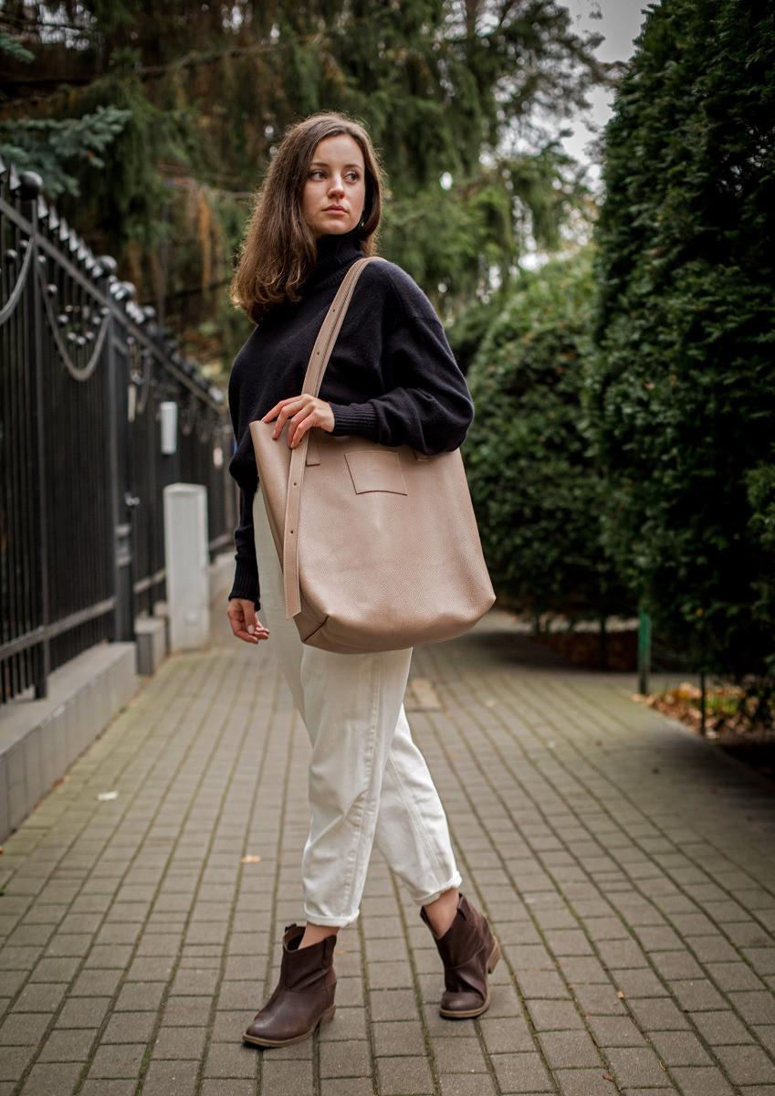 Torba Shopper Bag Nude Nasza wersja shopperki to największa i najpojemniejsza torba jaka dotąd powstała w studiu AGL Torba jest minimalistyczna w formie jednak posiada kilka bardzo praktycznych rozwiązań które czynią ją wyjątkową a także bardzo wygodną w użytkowaniu Ręcznie wykonana z najwyższej jakości włoskiej skóry naturalnej Rączki z sześcio stopniową regulacją dzięki której możemy zmieniać ich długość z krótkich po bardzo długie umożliwiające nawet założenie torby na krzyż w razie potrzeby Dwie kieszenie wewnętrzne większa do której zmieści się format A4 oraz mniejsza zamykana na zamek Wewnątrz 2 karabińczyki do których możemy przypiąć np klucze lub saszetkę z innej torby jak np z naszej Boxy Bag lub też Belt Pouch dzięki czemu zyskujemy jeszcze jedną kieszeń Otwór torby możemy znacznie zmniejszyć dzięki związaniu dwóch sznureczków znajdujących się wewnątrz torby wówczas zmieni ona lekko swój kształt i przybierze bardziej zwartą formę uniemożliwiającą zaglądanie do jej środka prze