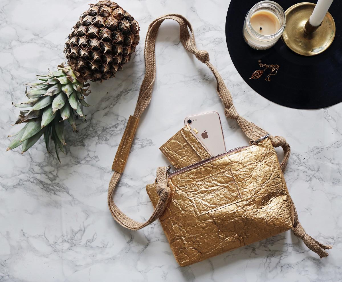 """Torebka Ananas Bag Gold to nasza pierwsza wegańska torebka wykonana z liści ananasa Torebka wykonana jest z Piñatexu nowatorskiego opatentowanego materiału premium który jest całkowicie wegański a jego produkcja jest odpowiedzialna i zrównoważona środowiskowo gdyż do jego wytworzenia używane są liście ananasa będące produktem ubocznym ekologicznych upraw ananasa na Filipinach Materiał ten jest ultra lekki i wodoodporny a zarazem bardzo wytrzymały elastyczny i oddychający Jego """"pognieciona"""" charakterystyczna struktura czyni go jedynym w swoim rodzaju a jednocześnie odpornym na zagniecenia W nielakierowanych wersjach z bliska widoczne są pojedyncze włókna surowca Zgodnie z zaleceniami producenta można go myć przy użyciu niewielkiej ilości wody i delikatnego detergentu Sama torebka mimo swoich niepozornych rozmiarów jest bardzo pojemna oraz posiada jedną wewnętrzną kieszeń jest również niezwykle lekka Zamykana jest na atestowany anty niklowy zamek metalowy Pasek torebki wykonany jest z na"""