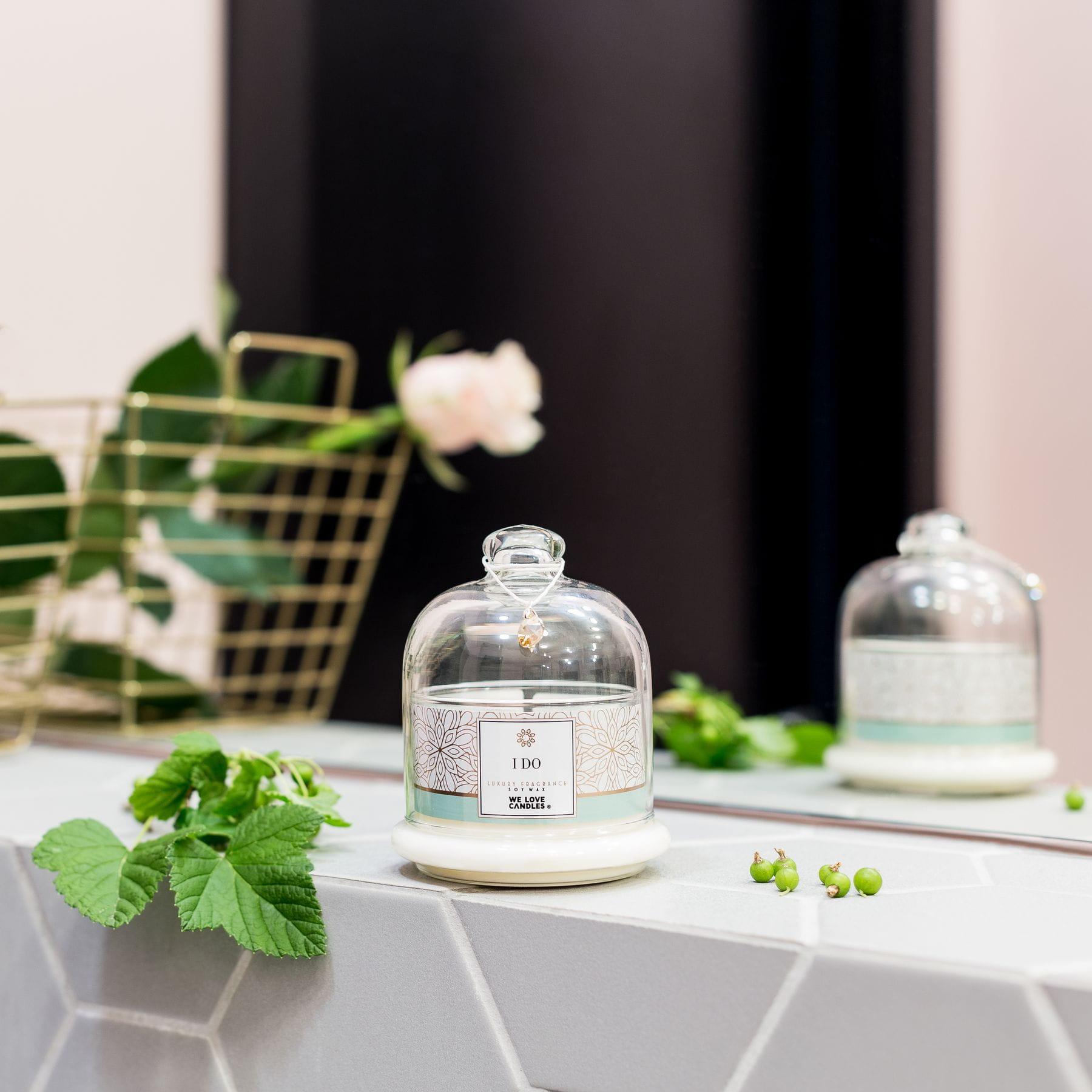 """Kolekcja świec zapachowych GOLD to wyjątkowo piękne świece sojowe, których walory zostały docenione wyróżnieniem w plebiscycie Influencer's Top 2019. Ich niezwykłe zapachy, które są inspirowane ponadczasowymi damskimi perfumami, zamknęliśmy w wyjątkowej urody, elegancki szklany pojemnik – w kształcie kopułki. Każdą świecę zdobi oryginały kryształek Swarovskiego, który później można zawiesić na łańcuszku. Dzięki tym zabiegom świece z kolekcji GOLD zachwycają pięknem formy, a urzekające zapachy sprawiają, że ich palenie można określić mianem """"luksusowej sensualnej przyjemności"""". I do Świeca I do to świeża, pełna wdzięku i lekkości kompozycja zapachowa oparta na trzech nutach zapachowych: czarnej porzeczki w głowie woni, frezji i róży w sercu oraz wanilii, ambroxanu, paczuli i drzewie sandałowym jako bazie. Poczuj przyjemną lekkość bytu, moc możliwości i potencjału, który drzemie w Tobie lub w sytuacji, z powodu której chcesz sięgnąć po tę niezwykle elegancką świecę. Kup w prezencie Po tę"""