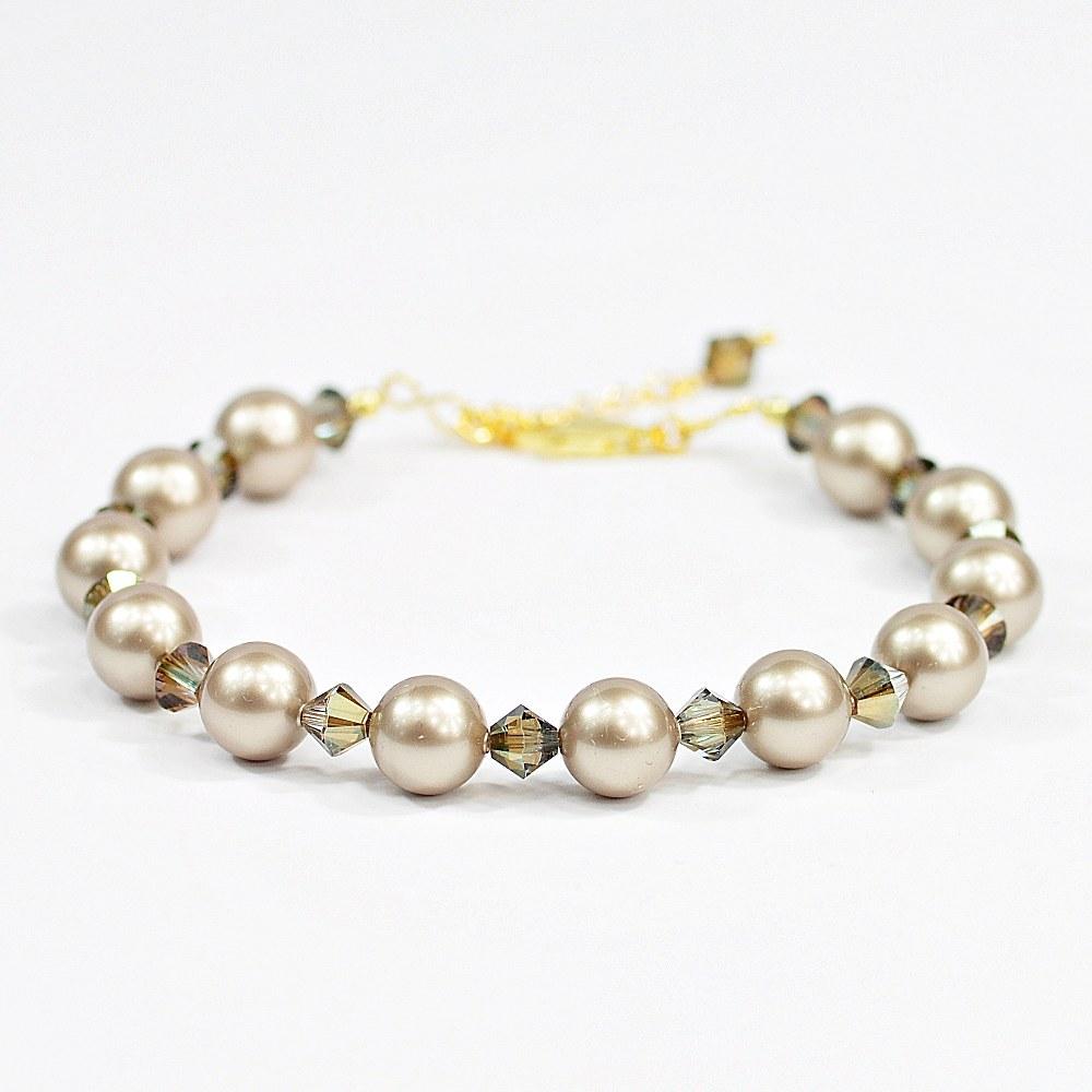 Bransoletka BP PlaZ to bardzo elegancka bransoletka wykonana z przepięknych, satynowych pereł Swarovskiego w kolorze Crystal Platinum oraz zjawiskowo lśniących kryształów Swarovskiego bicone w kolorze Crystal Bronze Shade. Wszystkie dodatkowe elementy wykonane są ze srebra 925 platerowanego 24 karatowym złotem. Biżuteria z pereł i ich imitacji to ponadczasowa klasyka, symbol elegancji, szyku i kobiecości, bransoletka będzie świetnym dodatkiem zarówno do dziennych, jak i wieczorowych stylizacji. obwód ok. 16,5 cm + 3 cm łańcuszka regulacyjnego zakończonego kryształkiem perły Swarovskiego Crystal Platinum - 8 mm kryształy Swarovskiego - bicone Crystal Bronze Shade - 5 mm zapięcie / karabińczyk - srebro 925 platerowane 24 karatowym złotem łańcuszek regulacyjny - srebro 925 platerowane 24 karatowym złotem - 3 cm pozostałe elementy - srebro 925 platerowane 24 karatowym złotem