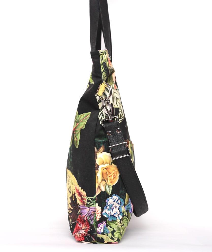 Duża torebka w kształcie prostokąta, która idealnie sprawdzi się wiosną i latem, doskonale pasuje do sukienek i kobiecych stylizacji. Możesz nosić ją na ramieniu lub na długim regulowanym pasku na skos – jak listonoszkę. Wyjątkowa torebka z pięknej tkaniny w kwiatowy wzór idealnie sprawdzi się jako torba do pracy lub na uczelnię. Bez problemu zmieścisz w niej niewielki laptop, książki, notatki lub dokumenty. W dwóch zewnętrznych kieszonkach możesz ukryć mniej cenne rzeczy. Doskonała torba dla kobiet chcących wyróżnić się w tłumie. Mocna tkanina jest odporna na tarcie i wilgoć, bardzo łatwo utrzymać ją w czystości. Całość zapinana na zamek. W środku posiada dwie kieszonki, w tym jedną zapinaną na zamek. Dodatkowo dwie kieszenie zewnętrzne. Materiał wierzchni: Piękny welur tapicerski, bardzo mocny i trwały. Łatwo utrzymać go w czystości piorąc w pralce (w temperaturze 30 stopni) lub ręcznie. Niewielkich zabrudzeń można pozbyć się czyszcząc materiał ręcznie bez obaw o jakiekolwiek uszkodz