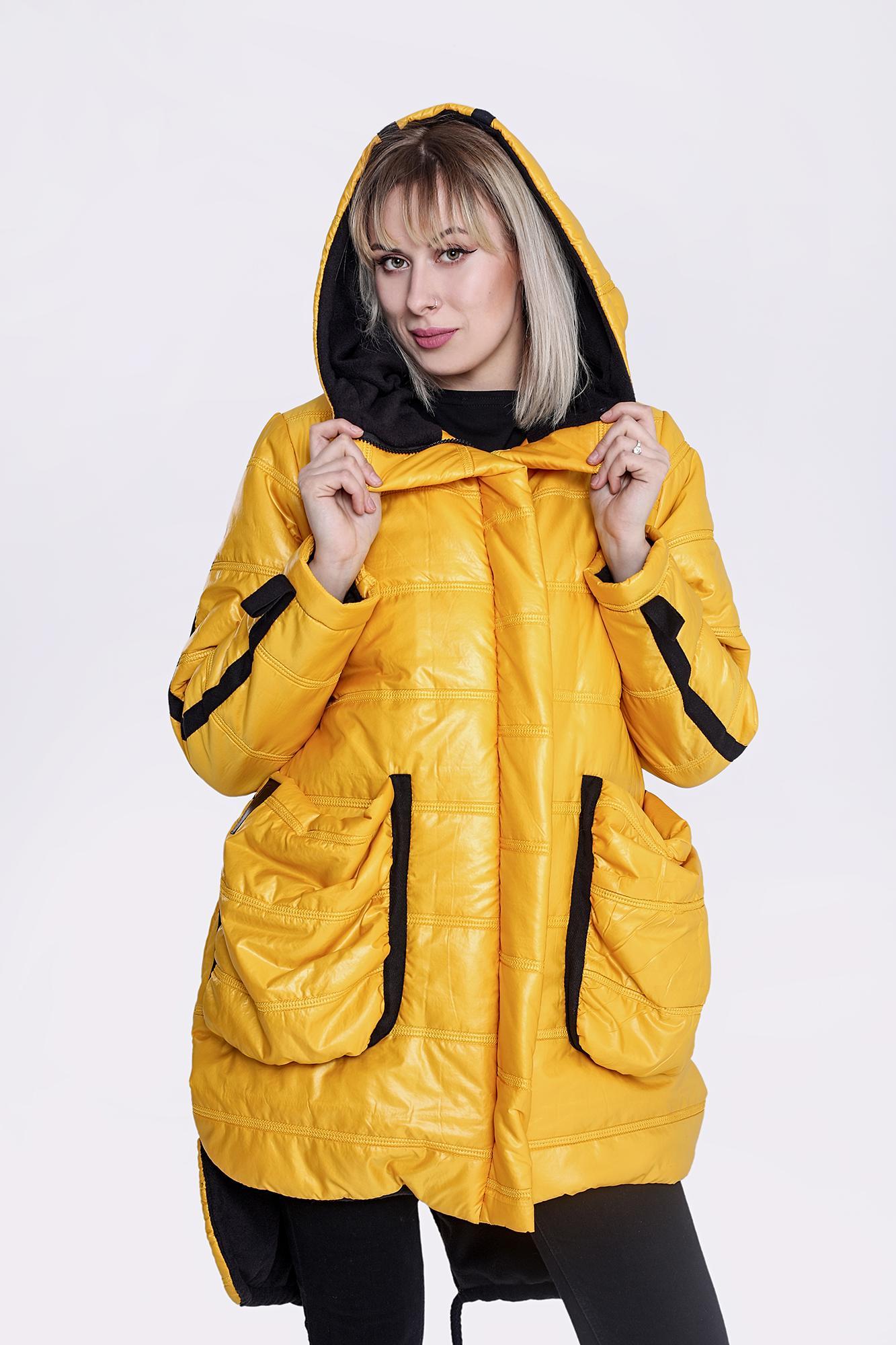 Pikowana, ocieplana kurtka w kolorze żółtym wykończona czarną, polarową podszewką. Charakteru dodaje jej wprowadzona asymetria, ogromne, marszczone kieszenie i naszywane taśmy w kapturze, na rękawach i kieszeniach, a także bawełniany gruby sznurek w kolorze czarnym.