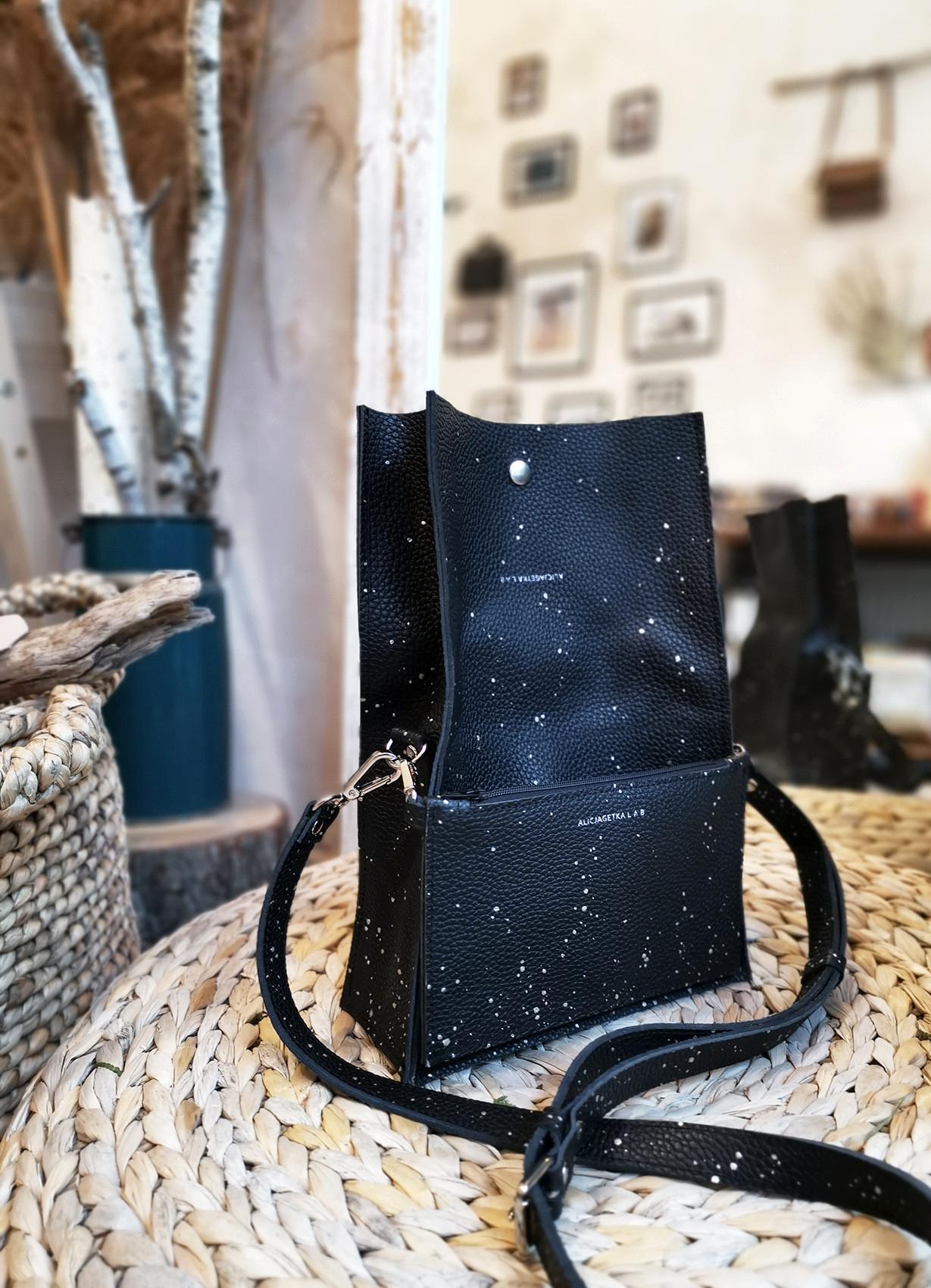 Torebka Boxy Bag S Night Sky dwuczęściowa torebka w specjalnej ręcznie malowanej limitowanej odsłonie Nasza wersja pojemnego pudełka którego kształt i wielkość zależy od zawartości noszonej w środku Modele z naszej wyjątkowej autorskiej linii Night Sky są ręcznie malowane metalizowaną wytrzymałą farbą do skóry w celu osiągnięcia efektu rozgwieżdżonego nieba setki różnego rozmiaru kropeczek tworzą na powierzchni niepowtarzalne konstelacje gwiazd każda sztuka jest unikatowa Warto zaznaczyć że każda kropeczka nanoszona jest osobno cieniutkim pędzelkiem nie jest chlapana Malowanie wraz z upływem czasu może delikatnie się wycierać w miejscach najbardziej narażonych na tarcie Skórzana torba z długą klapą zapinaną na napę klapa zgina się albo w połowie na wysokości zawartości włożonej do środka lub też utrzymuje się w pozycji pionowej kiedy torba jest bardziej wypełniona Skórzana zamykana kieszonka wewnątrz torby pełniąca funkcję organizera Zewnętrzna saszetka zapinana na suwak którą można pr