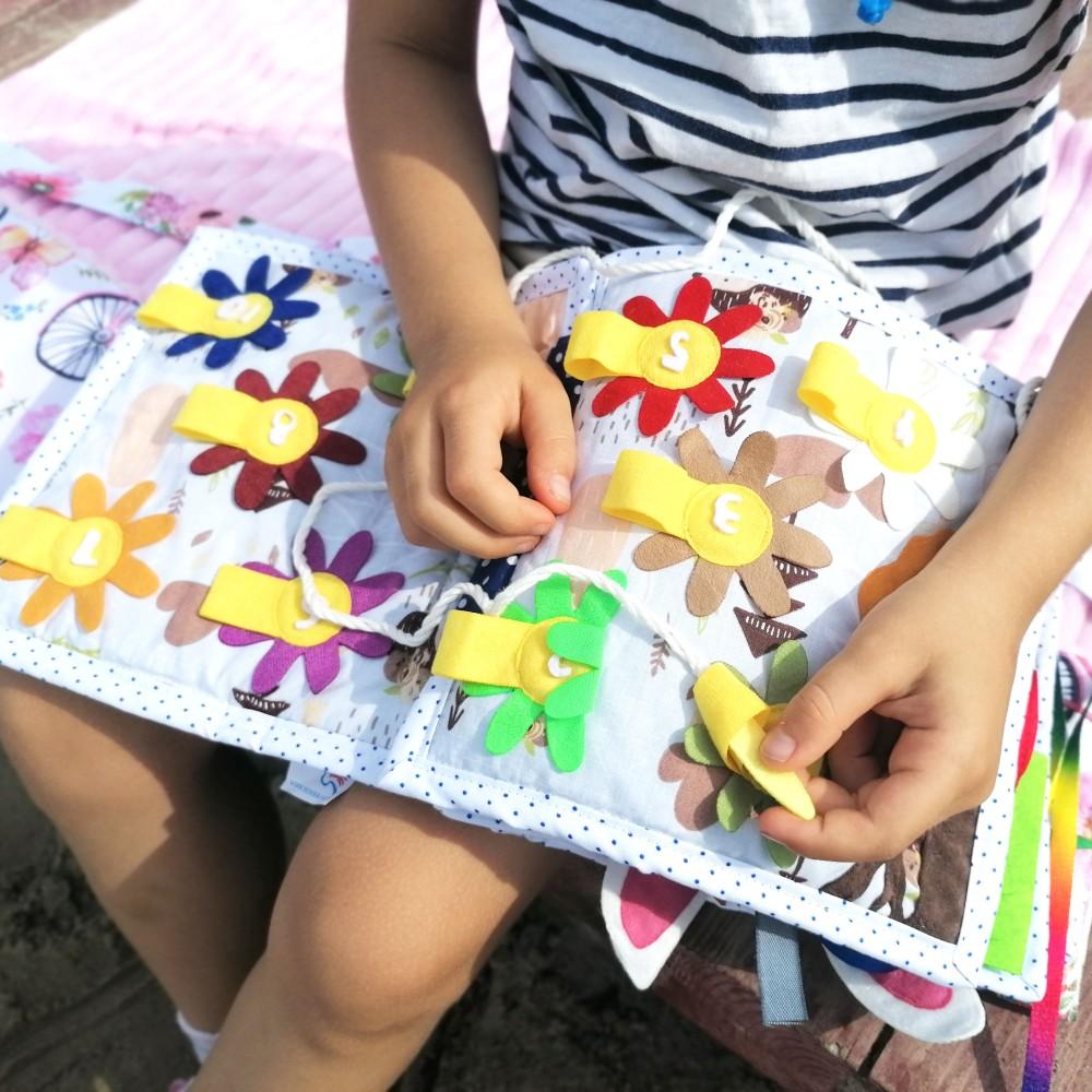 Książeczka zapinanki jest dedykowana dla dzieci powyżej 1,5 roku życia. Każda strona to oddzielna zabawa w zapięcia. Pierwsza strona to dopasowywanie kolorów oraz wielkości, czyli nauka proporcji. Dalej królik do złożenia, zapinany na napy. Każda łapka, główka, tłów mają oddzielne kolory napów, zatem układanie nie będzie takie proste. Balon - na tej stronie przygotowałam dwa rodzaje zapięć, napy oraz zawiązywanie, ubrane w zabawę w dopasowywanie chmurek. Zapinanie na guziki, to nasz ulubiona zabawa, zarówno 18 miesięczny syn, jak i 4 letnia córka zupełnie się przy niej zapominają. Pacynki w stodole, to przyjemność zabawy samemu, ale też z rodzicem. Kiedy moja córka testowała tego Bejbika, to byłą jej ulubiona poranna zabawa. W Zapinankach, znajdziemy też przekładanie przez szlufki. To zabawa, która niezwykle rozwija małą motorykę. Poprzez chwytanie pszczółki, po przekładanie jej przez szlufki, ale i odpowiednie ułożenie otworów, by jak najszybciej móc przełożyć przez nie pszczółkę. Ost