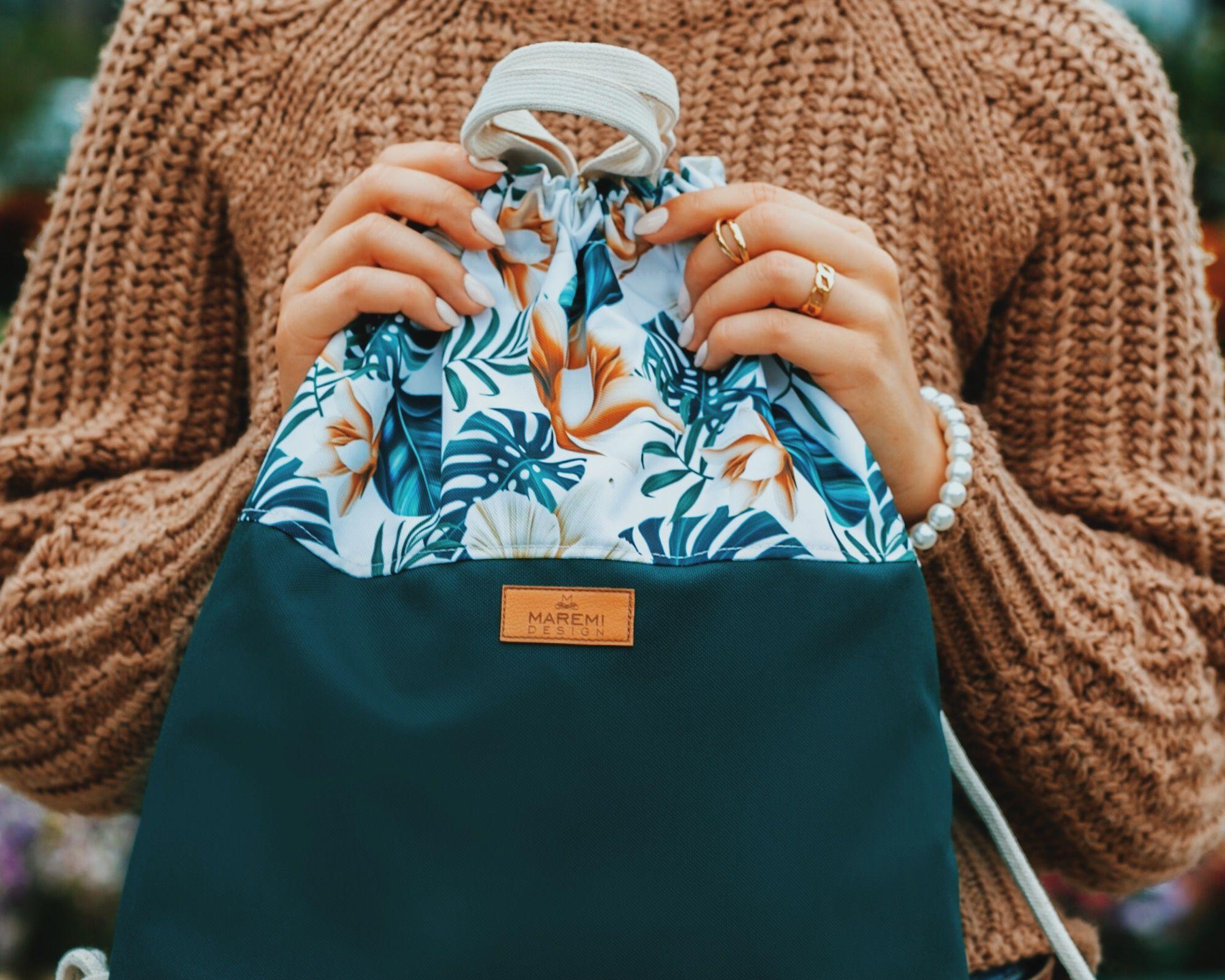 PLECAK WOREK JAKO ELEMENT MIEJSKIEJ STYLIZACJI. Wodoodporny plecak worek w print zielonych liści monstera oraz delikatnych kwiatów storczyka. Spód plecaka jest w kolorze głębokiej zieleni. Jest model, który z pewnością będzie pasował do wielu Twoich stylizacji. W środku jest wodoodporna, kaletnicza podszewka. Zamykana na suwak kieszonka na drobiazgi, karabińczyk na klucze lub inne rzeczy, które wyjmiesz jednym ruchem oraz niezwykle funkcjonalna bawełniana rączka do trzymania worko plecaka jak torebkę. Plecak szyty ręcznie, z najwyższą dokładnością a jego oryginalny wzór nie pozostawi nikogo obojętnym. Wymiary: (+/-2cm):Wysokość: 43cmSzerokość: 37cm Dno: 4 cm ZALETY: - kaletnicza i wodoodporna podszewka z zamykaną kieszonką na zamek- karabińczyk na klucze wewnątrz plecakoworka- gruby bawełniany sznur 8mm- wodoodporny- łatwość w utrzymaniu czystości- wytrzymałość- piękny designPIELĘGNACJA: - zalecane pranie ręczne- temp. prania do 30st. C- nie należy używać wybielaczy- prasować w niskiej